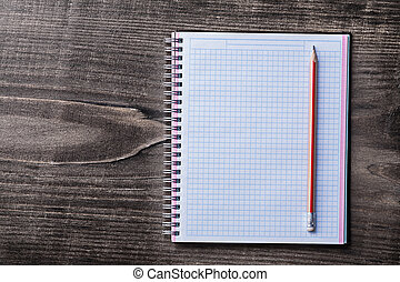 Red pencil and checked copybook on pine wooden board education c