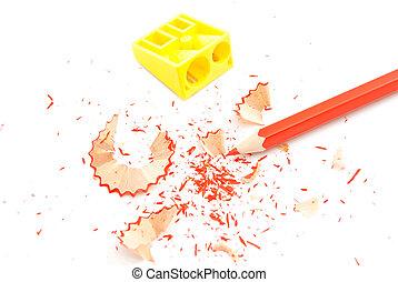 red pencil, pencil sharpener and shavings