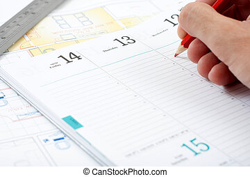 red pencil writing in a calender blue print in the background