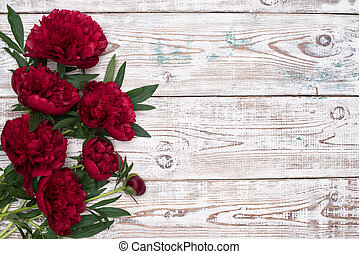 Red Peonies flowers on the white wooden table