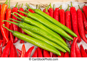 red pepper and green pepper on shelf in market.