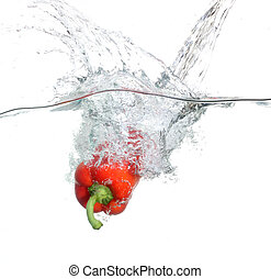 Red pepper falling into water over
