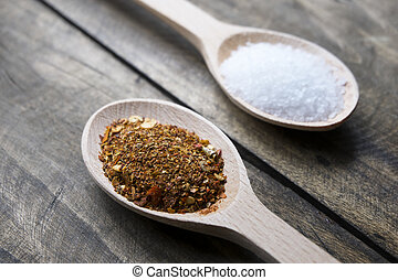 Red pepper flakes in wooden spoon, close up