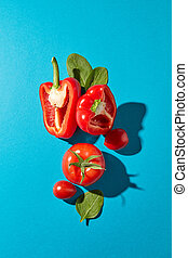 Red pepper halv, juicy tomatoes and spinach leaves with shadow reflection on a blue background with copy space. Ingredients for Salad. Flat lay