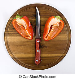 Red pepper on wooden kitchen board with knife