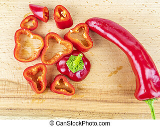 Red pepper sliced on a wooden cutting board.