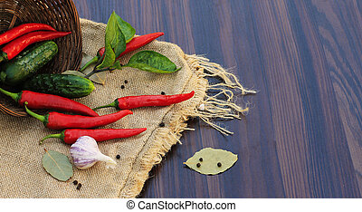 red pepper with leaves on sacking on the table with a basket