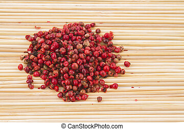red peppercorns, on chopping board