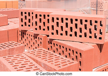 Red perforated bricks with rectangular holes closeup