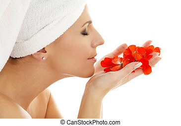 lovely woman smelling red flower petals