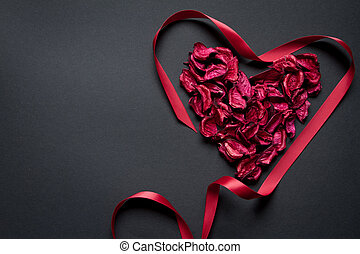 Red petals and silk ribbon shaped in the shape of a heart on a black background, congratulations concept