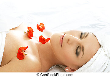 beautiful lady with red flowers in spa