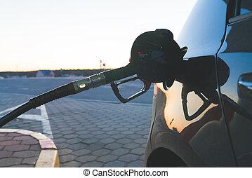 Red Petrol Pump Refueling Gun in the Tank of a Black Car