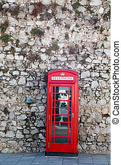 Red Phone Booth on Stone Wall