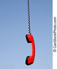 Red phone handset hanging against blue sky