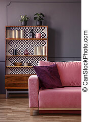 Red pillow on pink couch in retro living room interior with wooden cabinet. Real photo