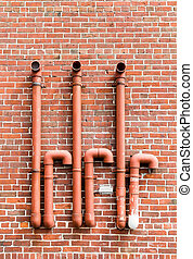 Red Pipes on Red Brick Wall
