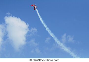 Red plane looping in a blue sky. Horizontal image