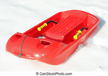 red plastic bob for play and to descend from the mountains with snow