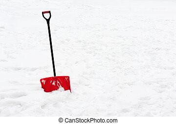 Red plastic shovel with black handle stuck in fluffy snow. -...