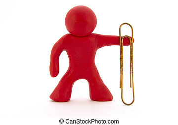 Red plasticine character and big paperclip. Stationery. Isolated over white background