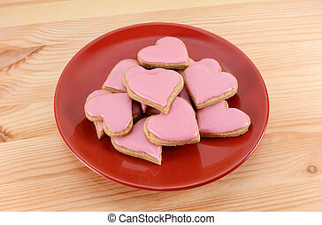 Red plate stacked high with iced heart-shaped cookies