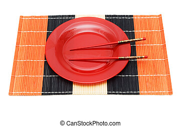 Red plate with chopsticks isolated on white