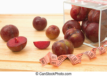 Red plum fruit with measuring tape in glass bowl , Diet fruit for weight loss