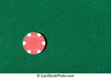 Red poker chip is on the table
