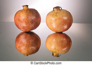 Red pomegranate on mirroring table. Gorizontal image with copy space. Gray background