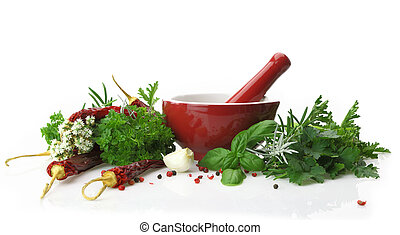 Red porcelain mortar and pestle with fresh herbs