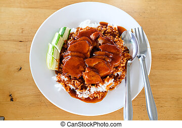 Red pork with rice and cucumber on a plate.
