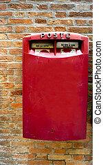 red postal box public on brick wall