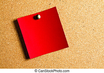 red postit hanging on a red panel of cork
