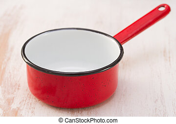 red pot on white wooden background
