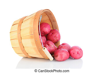 A basket of red potatoes tipped over and spilling onto the reflective surface. Horizontal format.