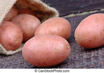 Red potatoes in a jute sack on table