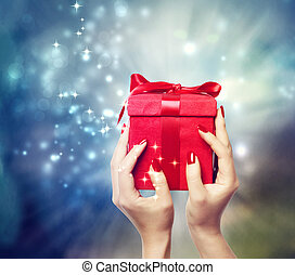 Red present box on Christmas on shinning background being held up by in a woman's hands