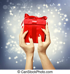 Woman's hands holding up red present box on Christmas on shinning background