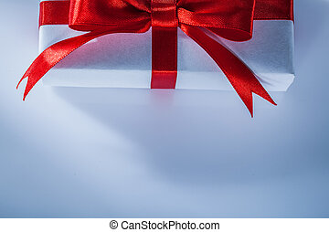 Red present box with knot on white background