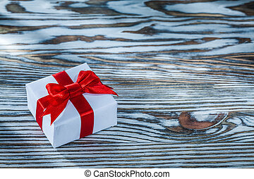 Red present box with knot on wooden background