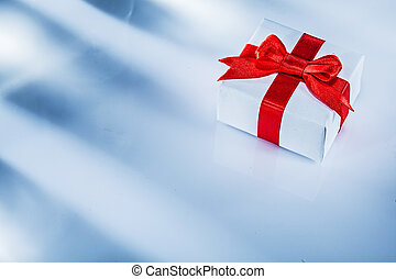 Red present box with tied bow on white background