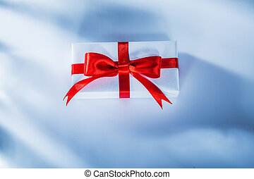 Red present box with tied ribbon on white background