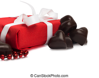 Red present box with white ribbon and candies in a shape of a heart isolated on white background