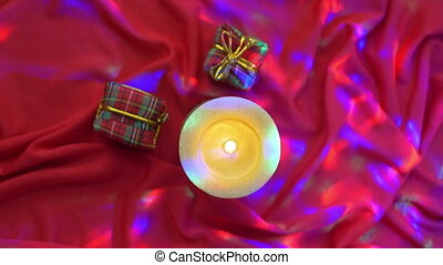 Red present boxes on silk background with lights and candle