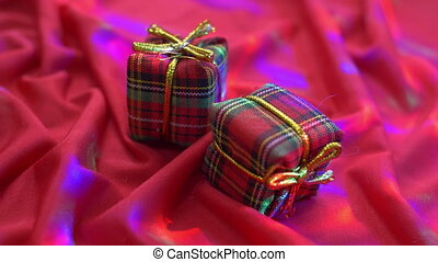 Red present boxes on silk background with lights