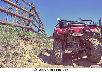 red quad bike on a dirt road, close-up, rear view