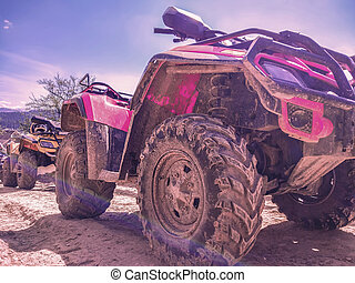 red quad bike on a dirt road, close-up, side and front view