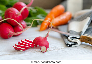 Red radish and carrots are on white wooden table.