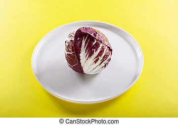 Red radish in the white plate on the yellow background